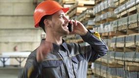 Ευτυχής βιομηχανικός εργάτης σε ένα hardhat χαμόγελο που μιλά στο τηλέφωνο φιλμ μικρού μήκους