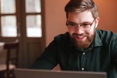 Ευτυχής γενειοφόρος νεαρός άνδρας που χρησιμοποιεί το φορητό προσωπικό υπολογιστή Στοκ Φωτογραφία
