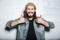 Ευτυχής γενειοφόρος τοποθέτηση ατόμων hipster με τους αντίχειρες επάνω στη χειρονομία Στοκ Εικόνες