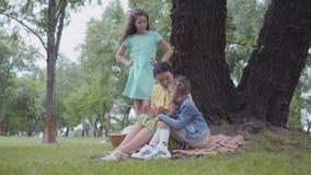 Ευτυχής γιαγιά πορτρέτου που διδάσκει τις εγγονές της καθμένος στο όμορφο πάρκο κοντά στο μεγάλο πράσινο δέντρο r απόθεμα βίντεο