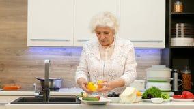 Ευτυχής γιαγιά που κατασκευάζει τη σαλάτα των φρέσκων λαχανικών φιλμ μικρού μήκους