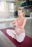 Ευτυχής γιόγκα κατάρτισης εγκύων γυναικών που διπλώνει τα χέρια Στοκ Φωτογραφία