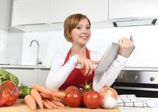 Ευτυχής γυναίκα εγχώριων μαγείρων στην ποδιά στην κουζίνα που χρησιμοποιεί την ψηφιακή ταμπλέτα ως cookbook Στοκ Εικόνες