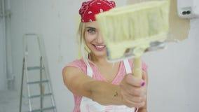 Ευτυχής γυναίκα ζωγράφος που δείχνει με τη βούρτσα φιλμ μικρού μήκους