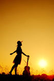 ευτυχής γυναίκα ηλιοβασιλέματος σκιαγραφιών κιθάρων Στοκ εικόνα με δικαίωμα ελεύθερης χρήσης