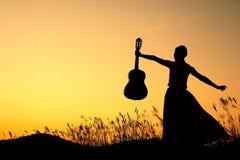 ευτυχής γυναίκα ηλιοβασιλέματος σκιαγραφιών κιθάρων Στοκ φωτογραφία με δικαίωμα ελεύθερης χρήσης