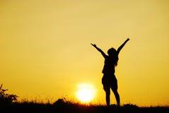 ευτυχής γυναίκα ηλιοβασιλέματος σκιαγραφιών Στοκ Εικόνες