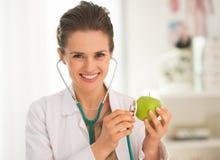 Ευτυχής γυναίκα ιατρών που εξετάζει το μήλο Στοκ φωτογραφία με δικαίωμα ελεύθερης χρήσης