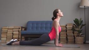 Ευτυχής γυναίκα ικανότητας που κάνει τις ασκήσεις τεντώματος και χαλάρωσης στο πάτωμα απόθεμα βίντεο