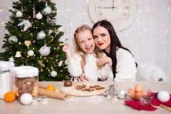 Ευτυχής γυναίκα και τα χαριτωμένα μπισκότα Χριστουγέννων κορών της μαγειρεύοντας στο Κ στοκ φωτογραφίες