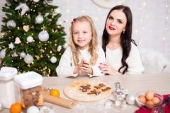 Ευτυχής γυναίκα και τα χαριτωμένα μπισκότα Χριστουγέννων ψησίματος κορών της στο ki στοκ φωτογραφία