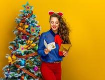 Ευτυχής γυναίκα κοντά στο χριστουγεννιάτικο δέντρο με την κάρτα ανάγνωσης φακέλων Στοκ Εικόνες