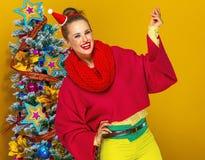 Ευτυχής γυναίκα κοντά στο χριστουγεννιάτικο δέντρο που σπάζει απότομα με τα δάχτυλα Στοκ Φωτογραφία