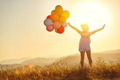Ευτυχής γυναίκα με τα μπαλόνια στο ηλιοβασίλεμα το καλοκαίρι Στοκ εικόνες με δικαίωμα ελεύθερης χρήσης