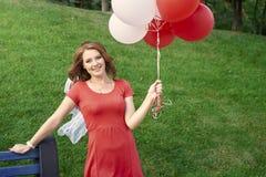 Ευτυχής γυναίκα με τα μπαλόνια στο πάρκο στοκ εικόνες