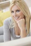Ευτυχής γυναίκα με τα μπλε μάτια που βάζει στον καναπέ Στοκ εικόνα με δικαίωμα ελεύθερης χρήσης