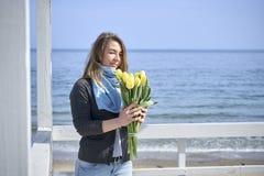Ευτυχής γυναίκα με τα λουλούδια κοντά στην ακροθαλασσιά στοκ φωτογραφία