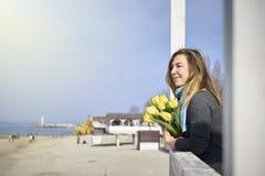 Ευτυχής γυναίκα με τα λουλούδια κοντά στην ακροθαλασσιά στοκ εικόνα με δικαίωμα ελεύθερης χρήσης