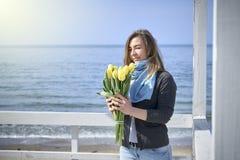 Ευτυχής γυναίκα με τα λουλούδια κοντά στην ακροθαλασσιά στοκ φωτογραφία με δικαίωμα ελεύθερης χρήσης