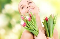 Ευτυχής γυναίκα με τα λουλούδια Στοκ Φωτογραφία