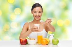 Ευτυχής γυναίκα με τα φρούτα, δημητριακά που τρώει το γιαούρτι στοκ φωτογραφία