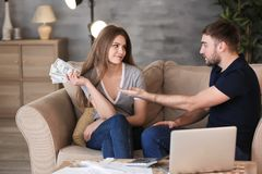 Ευτυχής γυναίκα με τα χρήματα και indignant άνδρας στον καναπέ στοκ εικόνες με δικαίωμα ελεύθερης χρήσης