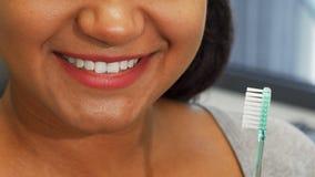 Ευτυχής γυναίκα με την τέλεια οδοντόβουρτσα εκμετάλλευσης χαμόγελου κοντά στο στόμα της απόθεμα βίντεο