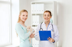 Ευτυχής γυναίκα με τη γάτα και το γιατρό στην κλινική κτηνιάτρων Στοκ Εικόνες