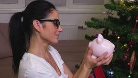 Ευτυχής γυναίκα με τη ρόδινη piggy τράπεζα φιλμ μικρού μήκους