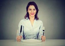 Ευτυχής γυναίκα με τη συνεδρίαση δικράνων και μαχαιριών στον πίνακα με το κενό πιάτο Στοκ φωτογραφίες με δικαίωμα ελεύθερης χρήσης