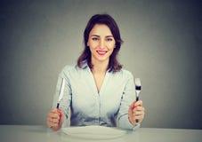 Ευτυχής γυναίκα με τη συνεδρίαση δικράνων και μαχαιριών στον πίνακα με το κενό πιάτο Στοκ εικόνες με δικαίωμα ελεύθερης χρήσης