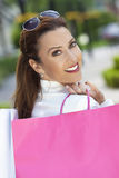 Ευτυχής γυναίκα με τις ρόδινες και άσπρες τσάντες αγορών Στοκ φωτογραφίες με δικαίωμα ελεύθερης χρήσης