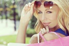 Ευτυχής γυναίκα με τις ρόδινες και άσπρες τσάντες αγορών Στοκ φωτογραφία με δικαίωμα ελεύθερης χρήσης