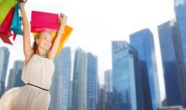 Ευτυχής γυναίκα με τις τσάντες αγορών πέρα από την πόλη Σινγκαπούρης στοκ εικόνα