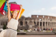 Ευτυχής γυναίκα με τις τσάντες αγορών πέρα από το coliseum στοκ φωτογραφίες