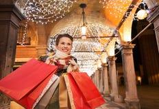 Ευτυχής γυναίκα με τις τσάντες αγορών που εξετάζει την απόσταση στη Βενετία Στοκ Εικόνες