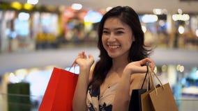 Ευτυχής γυναίκα με τις τσάντες αγορών στη λεωφόρο φιλμ μικρού μήκους
