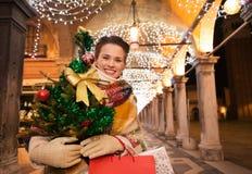 Ευτυχής γυναίκα με τις τσάντες χριστουγεννιάτικων δέντρων και αγορών στη Βενετία Στοκ φωτογραφία με δικαίωμα ελεύθερης χρήσης