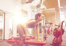 Ευτυχής γυναίκα με τους μυς κάμψης αλτήρων στη γυμναστική Στοκ Εικόνα