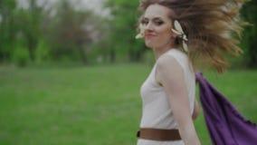 Ευτυχής γυναίκα με το ακρωτήριο που τρέχει πέρα από το πράσινο πάρκο φιλμ μικρού μήκους