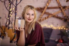 Ευτυχής γυναίκα με το δώρο κοντά στο χριστουγεννιάτικο δέντρο Στοκ Εικόνες