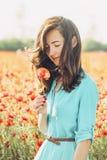 Ευτυχής γυναίκα με το λουλούδι παπαρουνών στον τομέα στοκ εικόνες