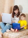 Ευτυχής γυναίκα με το μικρό παιδί που χρησιμοποιεί τα lap-top Στοκ φωτογραφία με δικαίωμα ελεύθερης χρήσης