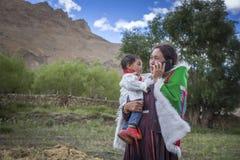 Ευτυχής γυναίκα με το χαριτωμένο μωρό μιλώντας σε κινητό Στοκ Φωτογραφίες