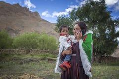Ευτυχής γυναίκα με το χαριτωμένο μωρό μιλώντας σε κινητό Στοκ φωτογραφία με δικαίωμα ελεύθερης χρήσης