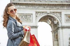 Ευτυχής γυναίκα με το χριστουγεννιάτικο δώρο κοντά Arc de Triomphe στο Παρίσι Στοκ Εικόνες