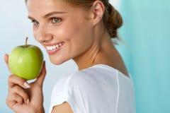 Ευτυχής γυναίκα με το όμορφο χαμόγελο, υγιής εκμετάλλευση Apple δοντιών Στοκ Φωτογραφία
