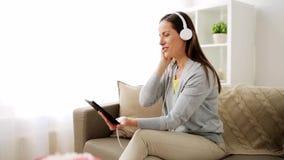 Ευτυχής γυναίκα με το PC ταμπλετών και τα ακουστικά στο σπίτι απόθεμα βίντεο