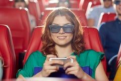 Ευτυχής γυναίκα με το smartphone στην τρισδιάστατη κινηματογραφική αίθουσα Στοκ Φωτογραφίες