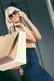 Ευτυχής γυναίκα μόδας με τις τσάντες αγορών που καλεί το κινητό τηλέφωνο Στοκ Φωτογραφίες
